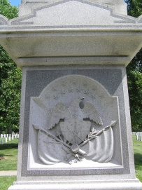 Section of the column adorned with an eagle and arms depicting Taylor's military service.