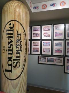 An over-sized replica of a Louisville Slugger bat dwarfs a collection of team photographs.