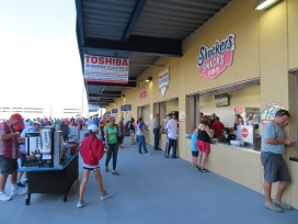 A trio of stands: Shuckers Snacks for desserts, Home Plate Hot Dogs, and Papa John's Pizza.