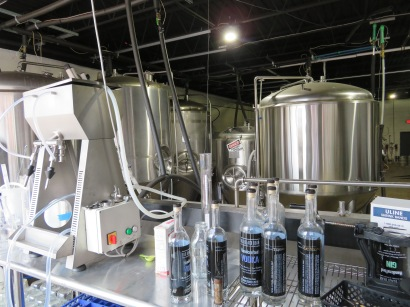 A view of the brewery's fermentation tanks with some unfilled bottles of vodka in the foreground.