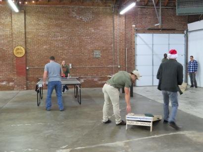 Visitors playing ping pong and cornhole.