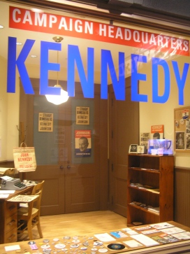 """The """"1960 Presidential Election"""" exhibit includes a mock Kennedy campaign office displaying a variety of campaign buttons, posters, and stickers."""