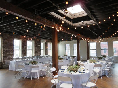 An overview of the brewery's event space being setup for a wedding reception.