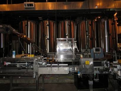 The brewery's canning line sits in front of the fermentation tanks.